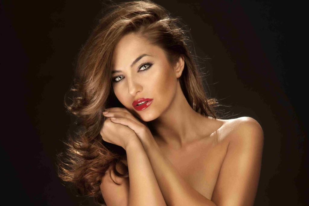 Portrait of sensual beauty with long curly hair wearing red lipstick and beautifyl makeup.